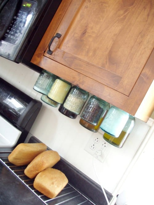 Mason Jars Hung from Cabinets - 150 Dollar Store Organizing Ideas and Projects for the Entire Home