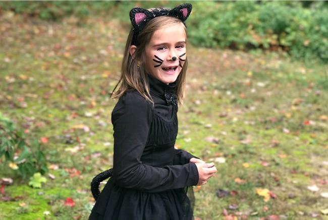 Girl in cat costume outside
