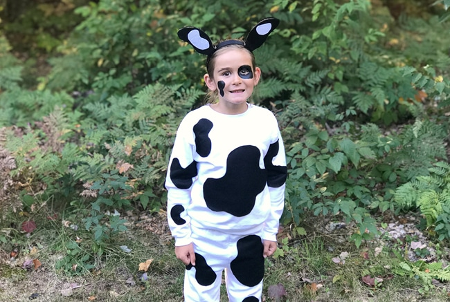 Girl in cow costume outside