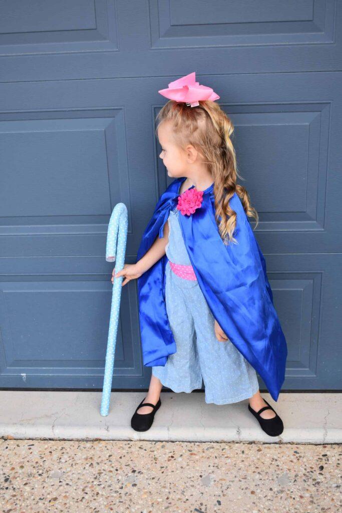 Girl in bo peep costume by garage door