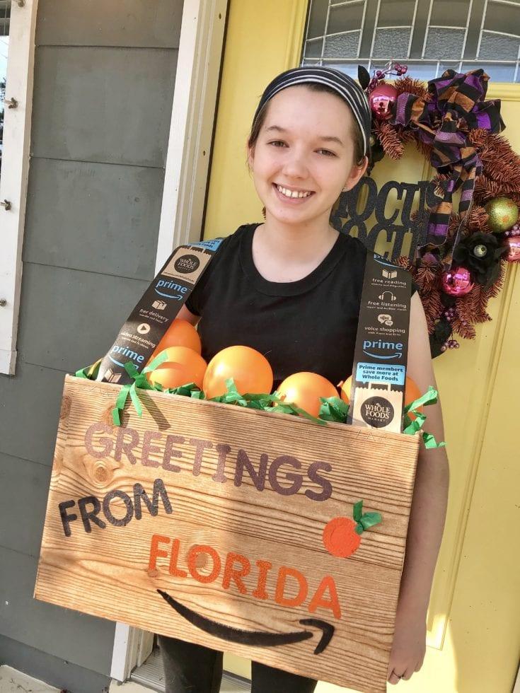 Girl wearing box of oranges