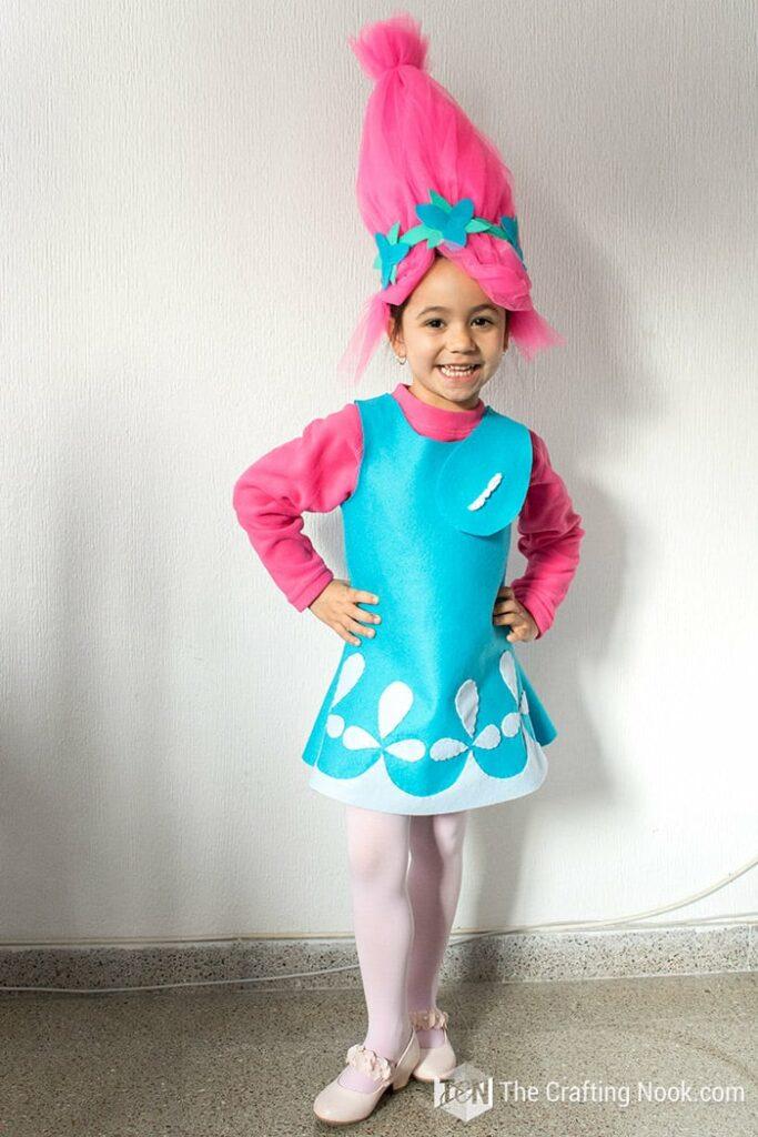 Gir in poppy costume by white wall