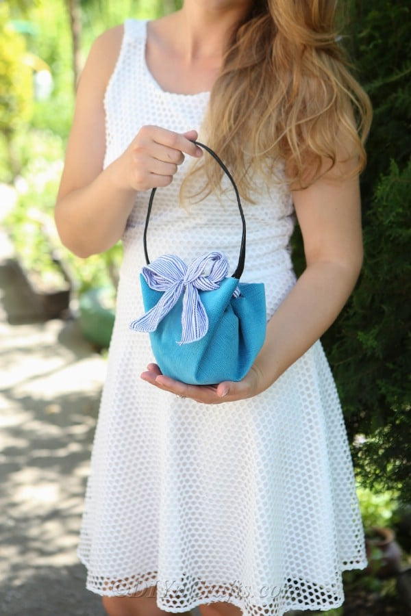 Woman in white holding blue bag