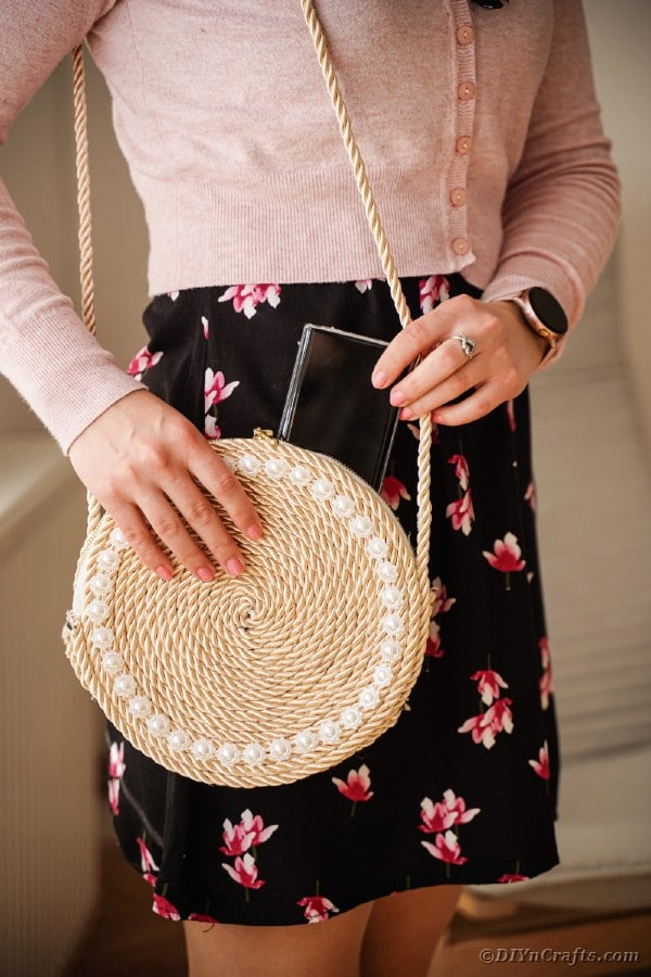 Woman in black skirt with rope purse