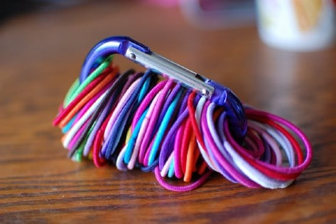 Use a carabiner to get your hair ties organized.