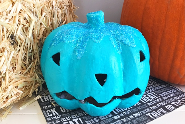 Teal pumpkin by hay bale