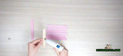 Use hot glue to attach 2 other sticks, one at either end, perpendicular to the rest. This holds them together in a square shape.