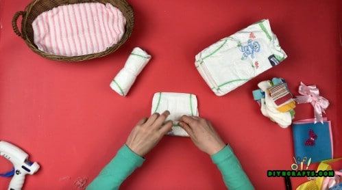 Roll up each diaper three times and use a pin or rubber bands to secure each one.