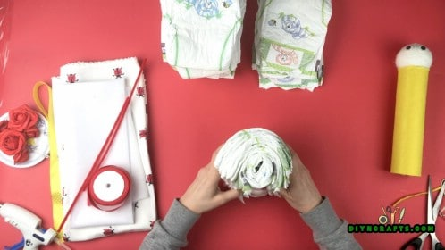 Roll up a single diaper, and then add a second diaper around it. Layer them up until you get about 6 diapers.