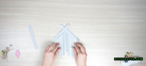 Get 2 more popsicle sticks and crisscross them. Glue them to the top to form the roof.