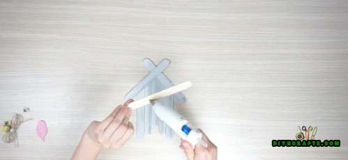 Get 1 more popsicle stick and glue it across the base of the house.