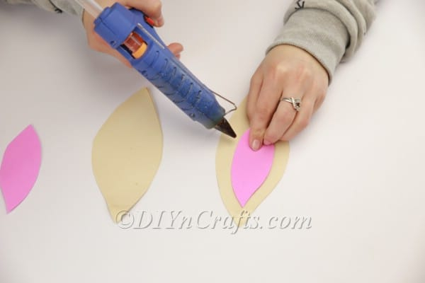 Using hot-glue gun to glue pink inner ears.