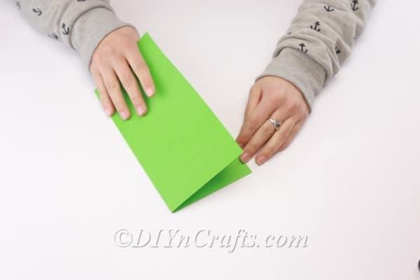 Folding the paper in half.