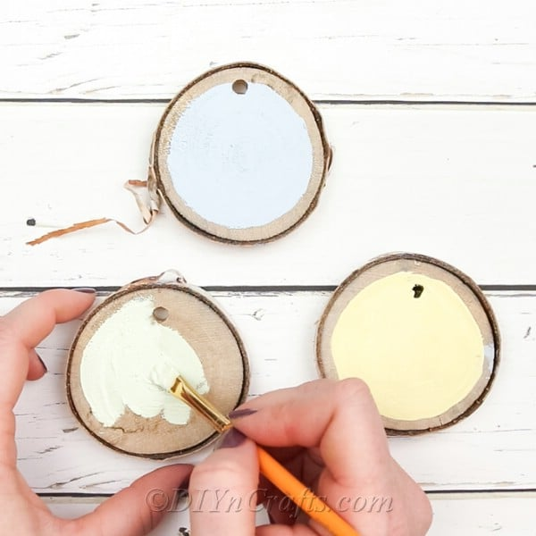 Paint wood slices in different colors of paint