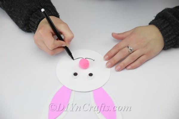 Glue the pink pom pom nose and draw the bunny's mouth.