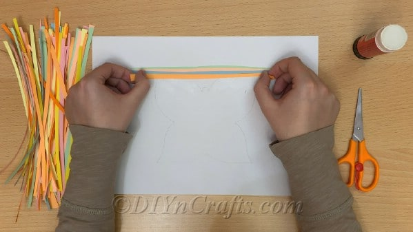 Add colored paper strips to plain paper and glue into place