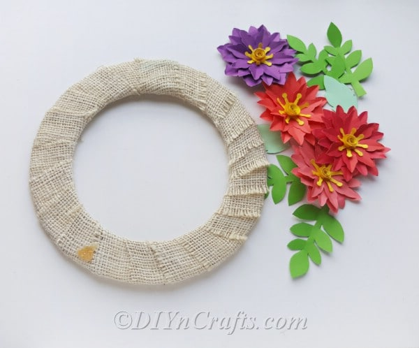 Use hot glue to attach flowers to wreath form