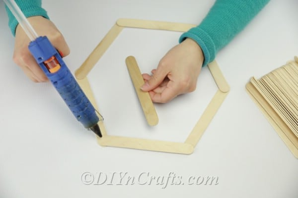Putting together DIY popsicle stick shelf