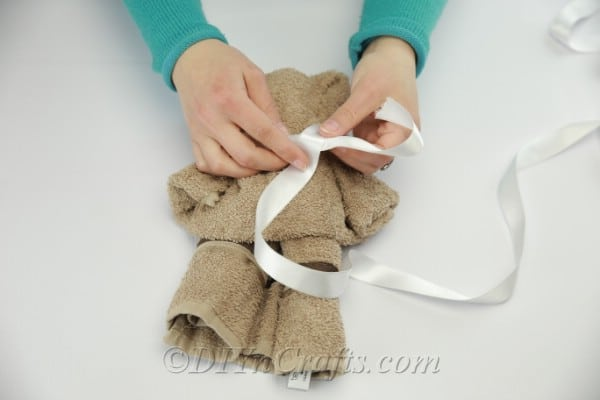 Tying ribbon around the neck of washcloth teddy bear
