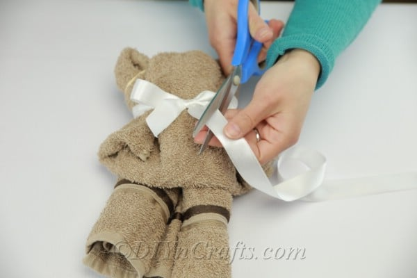Trimming ribbon on a washcloth teddy bear