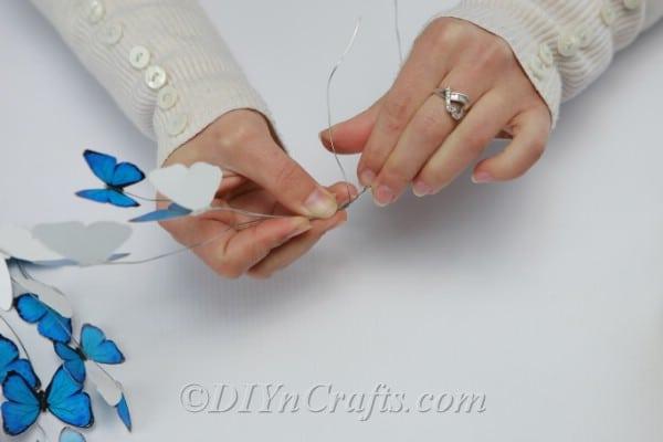 Folding a blue paper butterfly in half