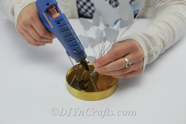 Using hot glue to attach the butterflies to the lid