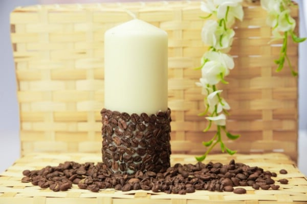 Coffee bean candle sitting in a bed of coffee beans