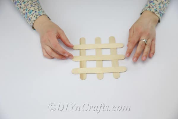 Laying craft sticks down to create a coaster