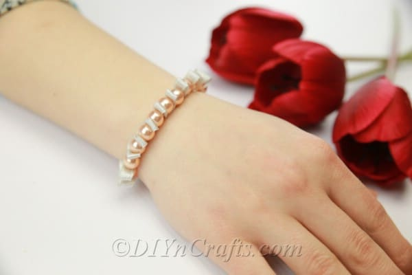 Pearl and ribbon bracelet being worn