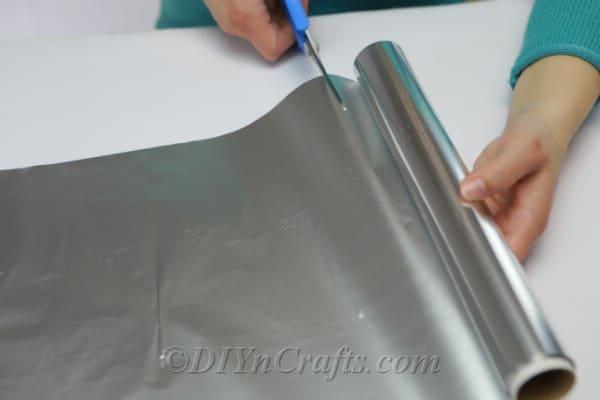 Cutting aluminum foil to cover a jar