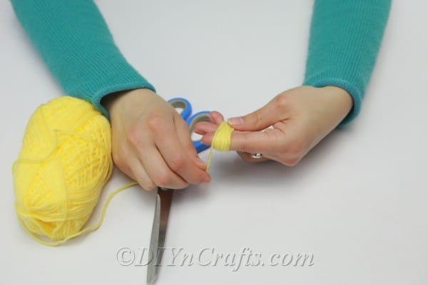 Wrapping yarn around fingers to create a tassel