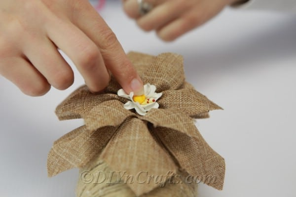 Gluing an artificial flower onto the burlap ribbon