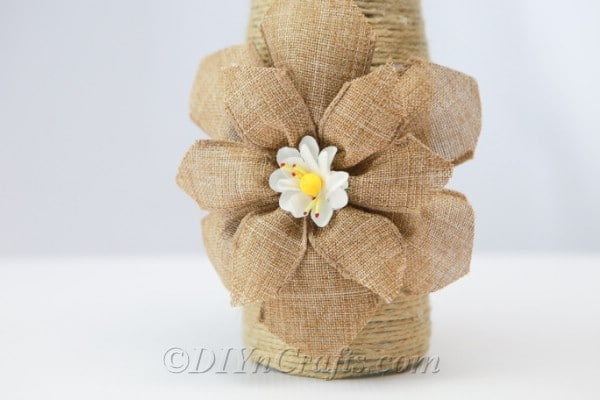 Rope covered bottle with a burlap flower decoration