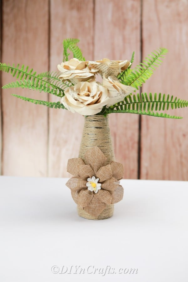 Rope covered bottle with paper flowers close up