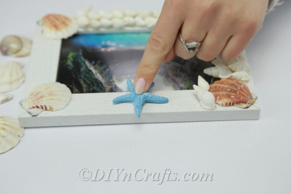 Adding decorations to finished seashell picture frame