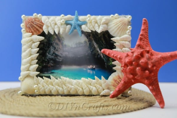 Shell covered frame with a red starfish on the side