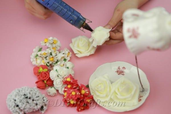 Gluing flowers onto teacup craft