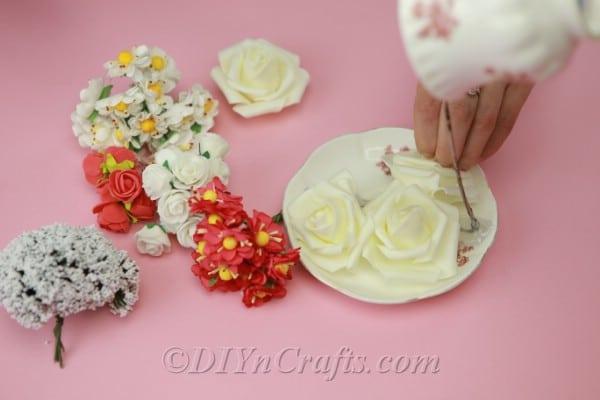 Gluing artificial flowers onto a saucer