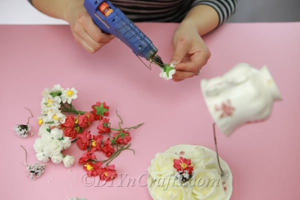 Continue to glue flowers onto cup, saucer, and wire
