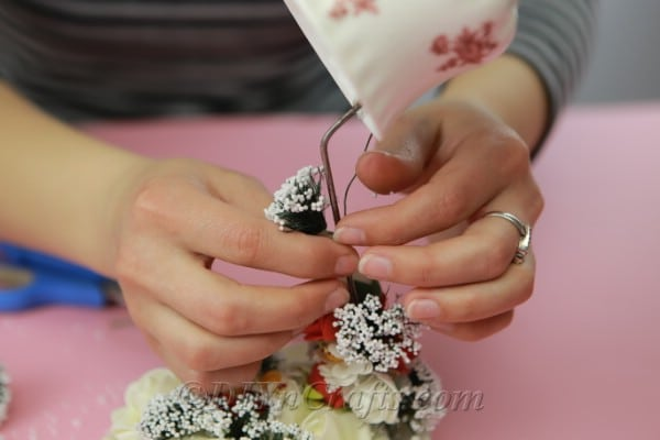 Gluing more flowers onto the wire