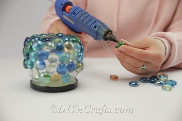 Continuing to glue glass stones onto a jar