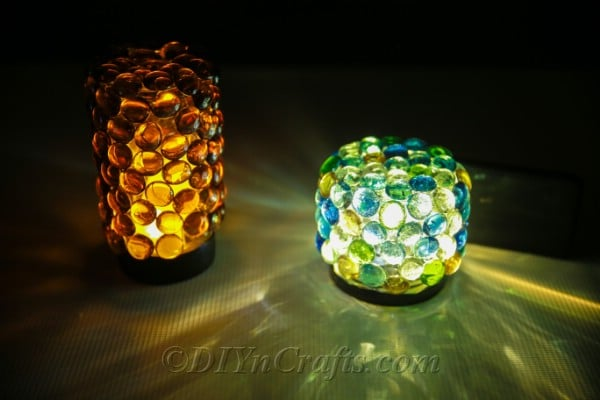 Two glass stone covered jars