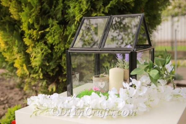 Mini greenhouse decorated with candles.