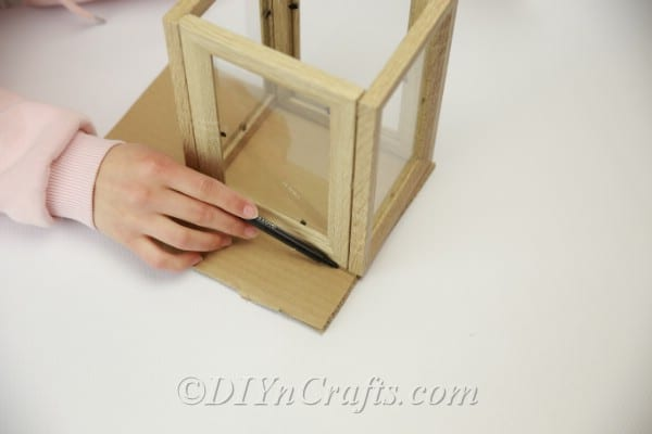 Measuring cardboard to fit the bottom of the lantern