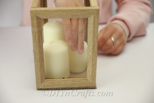 Adding seashells and candles to picture frame lantern