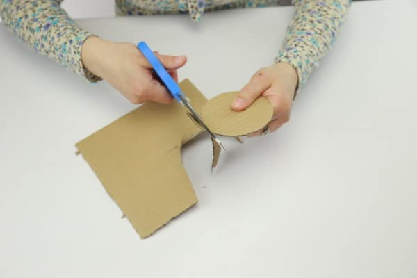 Cutting cardboard into circle for candle holder
