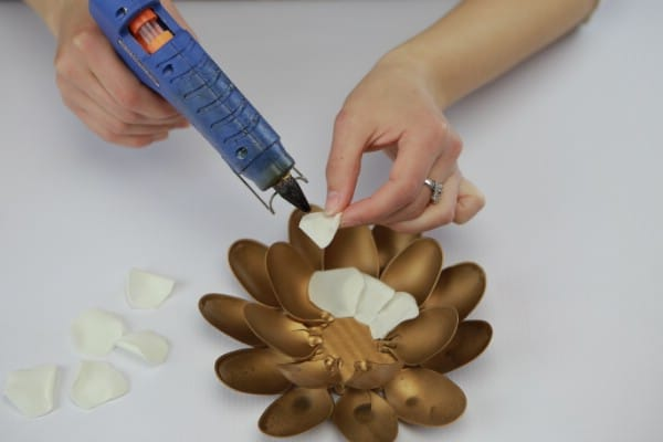 Gluing faux flower petals onto spray painted base