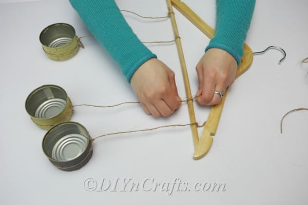 Hanging tuna cans from a wooden clothes hanger with twine