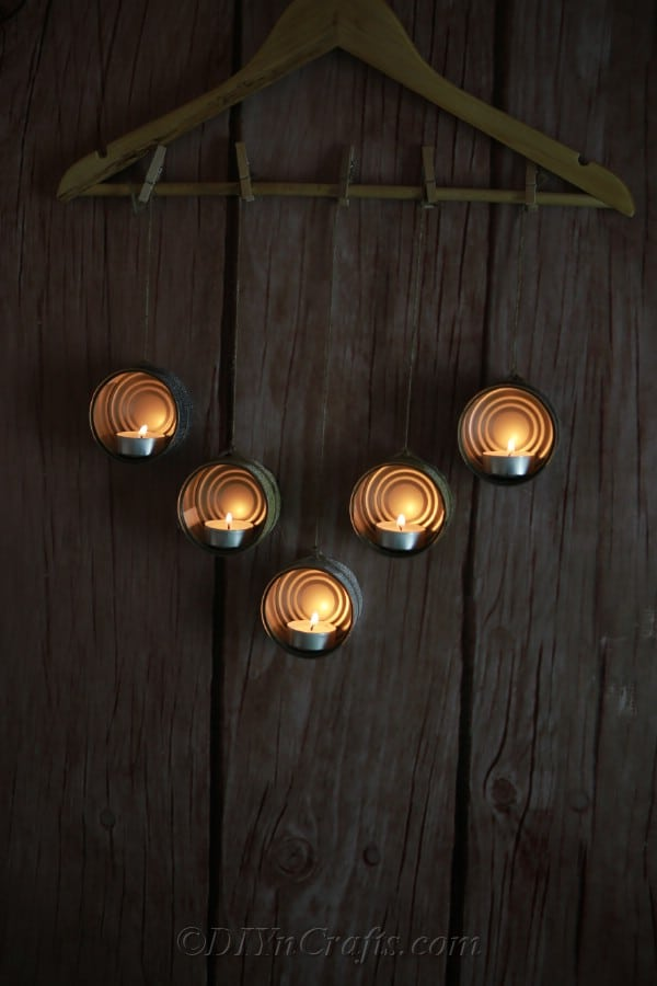 Tuna cans turned into candleholders and hanging from a wooden hanger