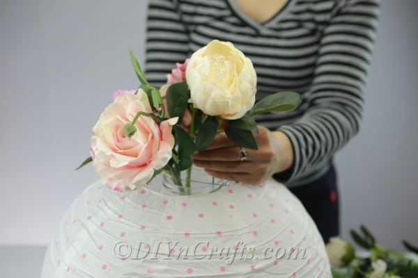 Adding flowers to a DIY paper lantern vase